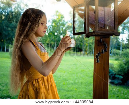 Little cute blond girl with a candle and a garden lantern