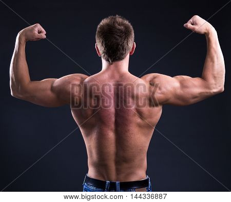 Back View Of Muscular Man Showing His Muscles Over Black Background
