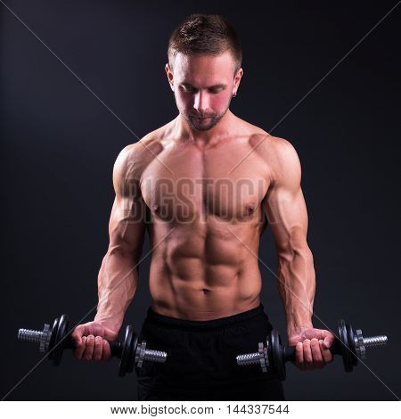 Portrait Of Young Handsome Muscular Man With Dumbbells Over Grey