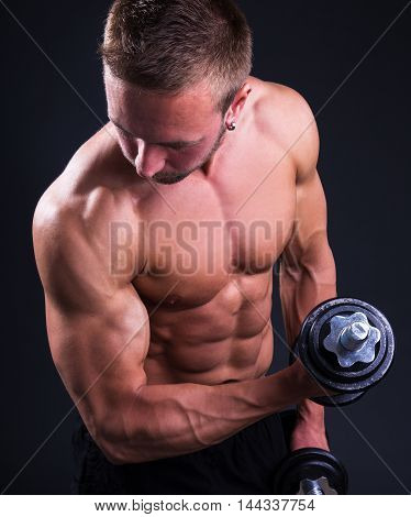 Young Muscular Man Doing Exercises With Dumbbells Over Grey