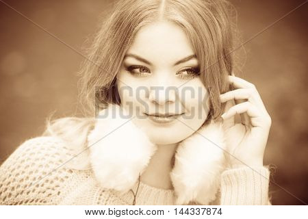 Smiling lady portrait. Young blonde girl in warm clothing sitting in autumnal park
