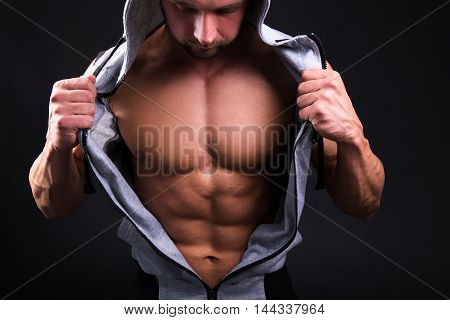 Young Muscular Man Showing His Torso Over Grey
