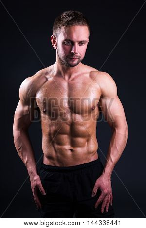 Portrait Of Young Muscular Man Standing Over Grey