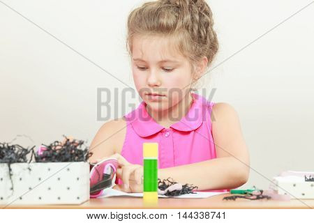 Little girl draw in the classroom. Being creative in elementary age. Searching accessories