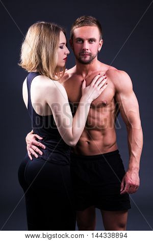 Love And Sport Concept - Sexy Woman And Muscular Man Over Grey