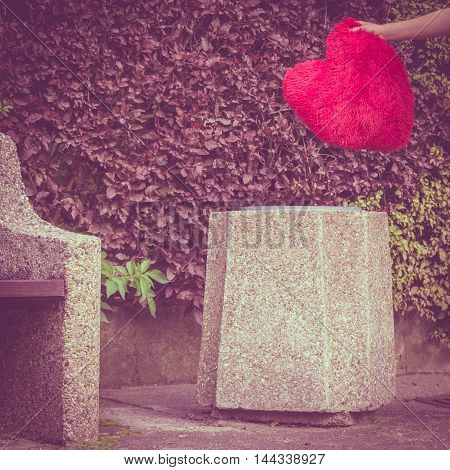 Love and feelings. Woman hand with big red heart on trash can. Hurt and depressed person throwing out sign of loving.