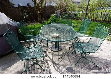 Green wrought iron furniture on the concrete patio in a back yard of a home in Joliet, Illinois.