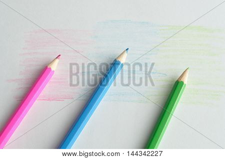 Three coloring pencils displayed on a white background that is colored in the same color as the pencils
