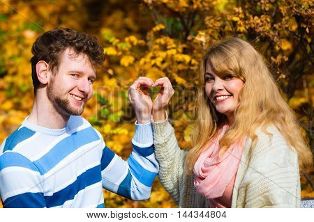 Young Lovers In Autumnal Park Make Heart Gesture.