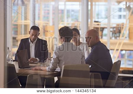 Group of four dynamic business executives sitting toether in a meeting about their company's future in the firms newly renovated conference room.