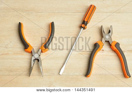 A long nose pliers screw driver and a pliers isolated on a wooden background