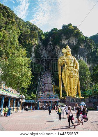 KUALA LUMPUR MALAYSIA - MAR 1: Tourist and Lord Murugan Statue in front the batu cave entrance on March 1 2016 in Kuala Lumpur Malaysia. A popular tourist attraction north of Kuala Lumpur.