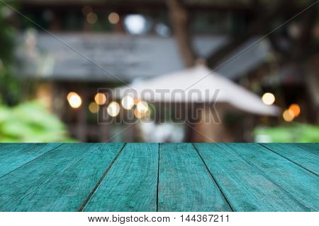 Blue wooden table top with cafe blurred abstract background