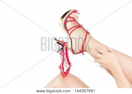 Woman putting off her red garter playing with it and her shoe. Over a white background isolated.