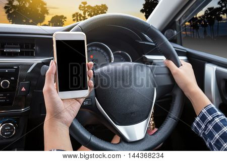 Young woman driver using touch screen smartphone and hand holding steering wheel in a car with palm tree at sunset or twilight background