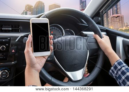 Young woman driver using touch screen smartphone and hand holding steering wheel in a car with city at twilight time background