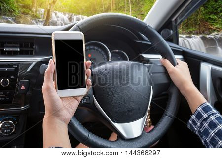 Young woman driver using touch screen smartphone and hand holding steering wheel in a car with waterfall and forest background