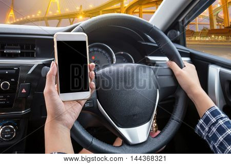 Young woman driver using touch screen smartphone and hand holding steering wheel in a car with modern bridge at night time background