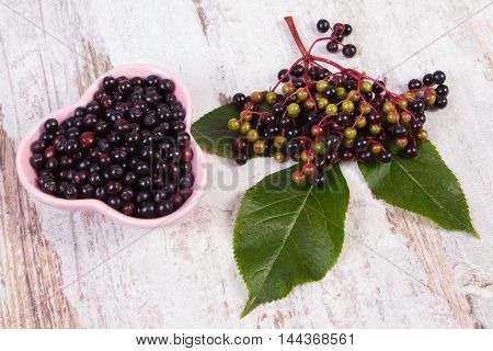Fresh elderberry with green leaf in glass dish on old rustic wooden background healthy nutrition alternative medicine and therapy