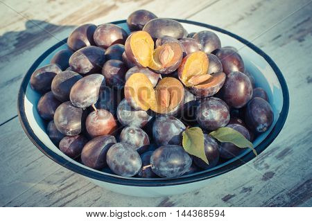 Vintage Photo, Heap Of Plums In Metal Bowl On Wooden Table In Garden On Sunny Day