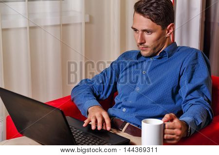 Man works for laptop. Businessman holding a cup of coffee. Freelancer at work.