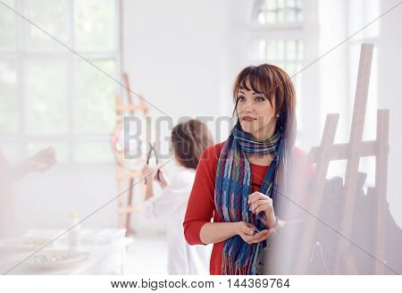 woman artist on workshop colorful glass mosaic indoor with little girl on background