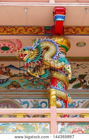 Golden Chinese dragon Wrapped around red pole at Chinese temple bacony.
