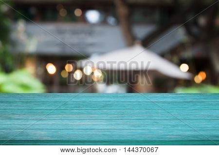 Top of blue wooden table with cafe blurred abstract background