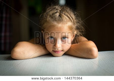 Portrait of a little girl at the table.