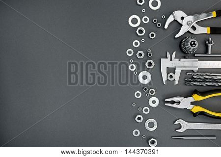 Set Of Different Hand Work Tools With Chrome Nuts On Gray Background