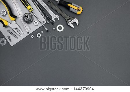 Top View Grey Background With Screwdrivers, Bolts, Spanner, Wrench, Pliers And Metal Plate