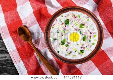 chciken greens and vegetables cold No-Cook soup with greek yogurt in clay bowl on table napkin with wooden spoon view from above