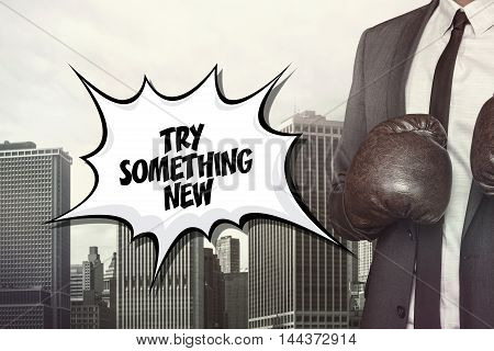 Try something new text on speech bubble with businessman wearing boxing gloves