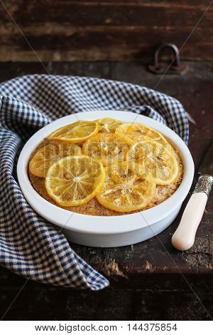 Citrus cake with lemon caramel slices on top in a baking dish on a wooden table, selective focus