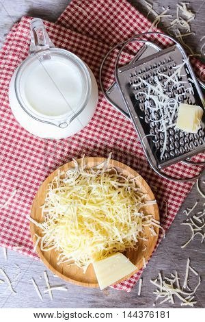 Ingredients for pasta cheese sauce or pizza, freshly grated parmesan or cheddar hard cheese, raw milk in a pot, kitchen tools, grater, wooden plate and kitchen towel, rustic vintage style