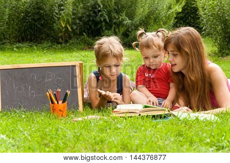mother teaches her young child letters. Early child development