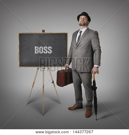Boss text on  blackboard with businessman holding umbrella and suitcase