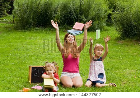 family. Mother and children are doing lessons and thrown the book