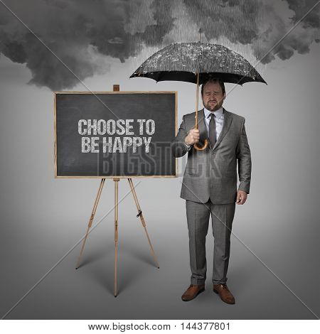 Choose to be happy text on blackboard with businessman holding umbrella