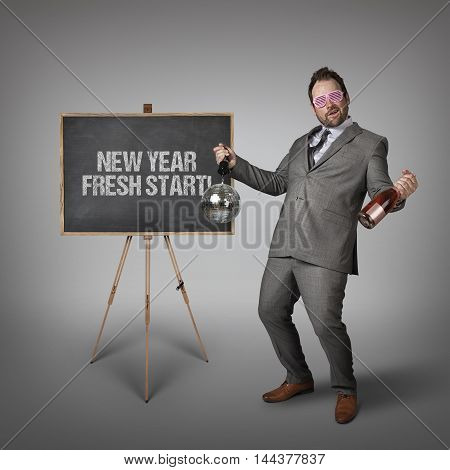 New year fresh start text on  blackboard with drunk businessman