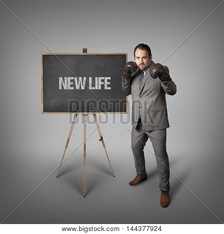 New life text on  blackboard with businessman wearing boxing gloves