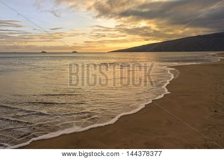 Sugar beach Kihei Maui Hawaii at sunset as a wave washes over the sand