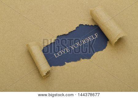 Love yourself message written under torn paper.