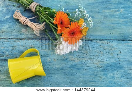 pretty flowers with yellow can on a blue plank