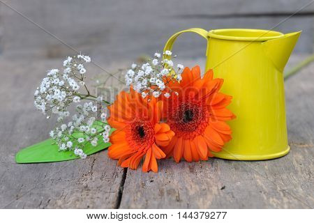 pretty flowers on a wooden background with colorful can and tool