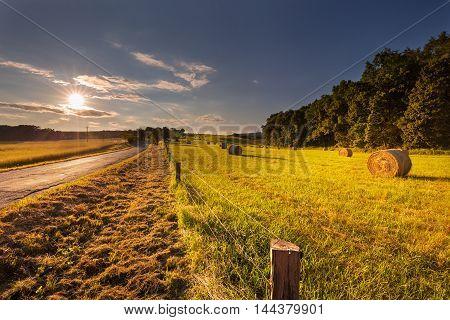 Meadow with straw bales illuminated sunrays. Motavian landscape Bacov.