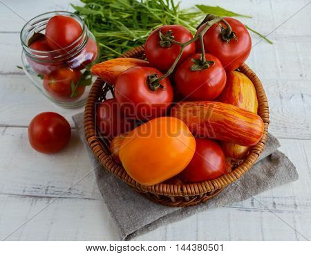 Basket with tomatoes of different varieties and arugula sheaf on white wooden background.