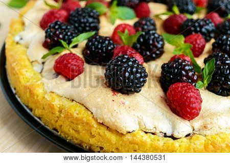 Pie (Tart) with fresh blackberries and raspberries air meringue decorative mint. Close up