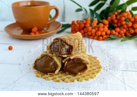 Homemade honey wafers rolled into a cone filled with caramel (condensed milk) rowan berries on a white background. Close up