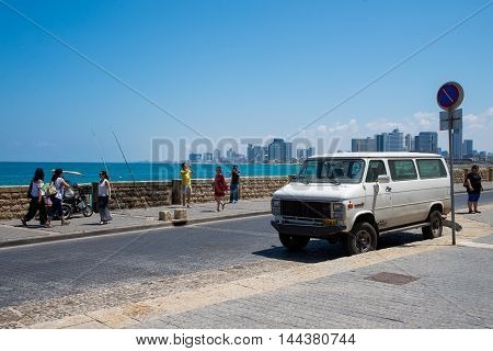 TEL AVIV, ISRAEL - JUNE 5, 2015: Tourists stroll along the promenade in the old town